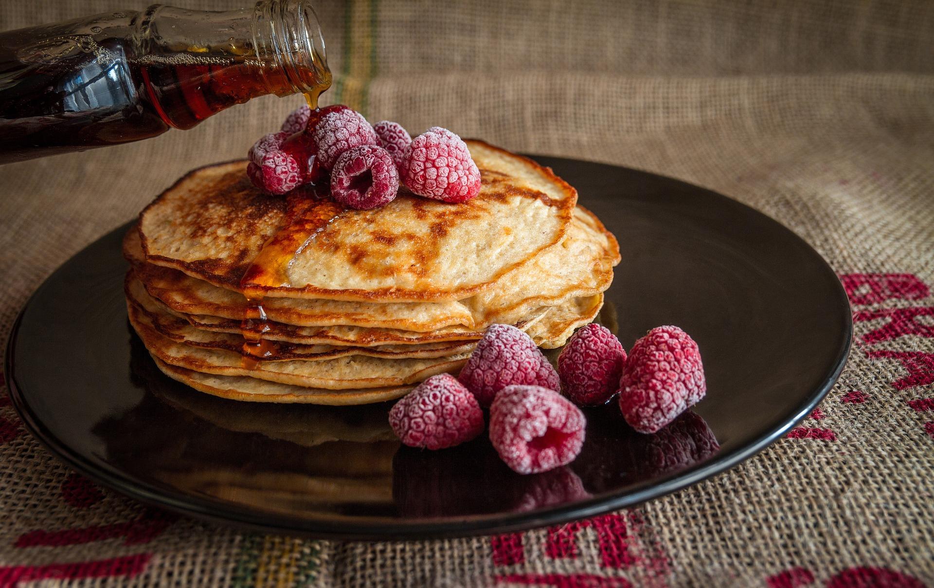 Pancakes mit Himbeeren und Ahornsirup.